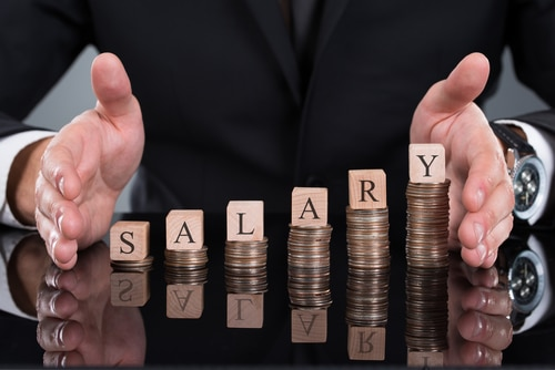 The word salary in wood blocks on a coin pile