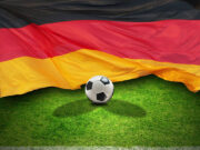 Germany flag with a soccer ball on grass field